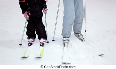 Mother with daughter stand on skis at background of snow slope