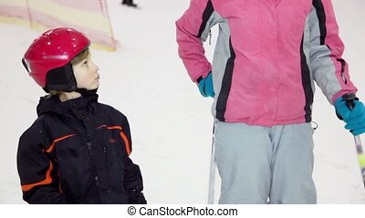 Mother with daughter stand on skis at background of people