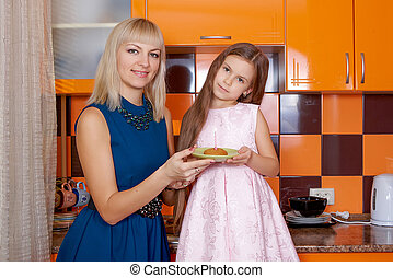 Mother with daughter standing in kitchen