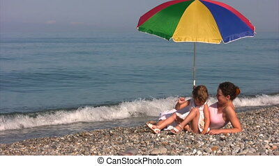 mother with daughter under umbrella on shore