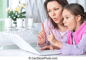 Mother with daughter using laptop