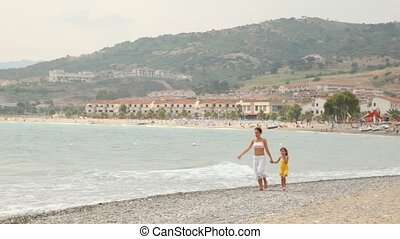 Mother with daughter walk keeping for hands on sea coast