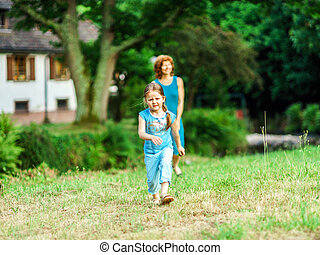 Mother with daughter walking in a village