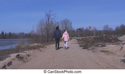 Mother with daughter walking on sand path