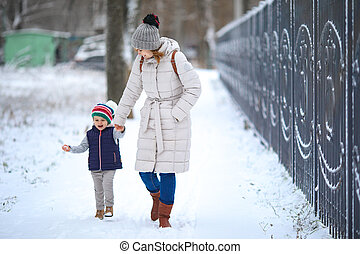 mother with daughter walks in snow-covered Park.