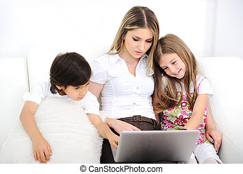 Mother with daugther and son using  laptop on sofa