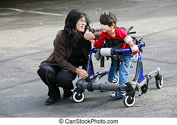 Mother with disabled son walking outdoors with walker, ...