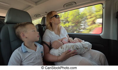 Mother with elder son and baby daughter traveling by car
