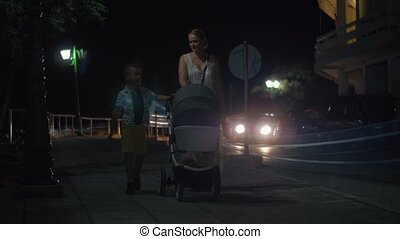 Mother with elder son and baby walking in the evening
