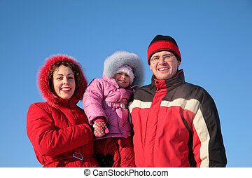 mother with father hold child on the hands in winter