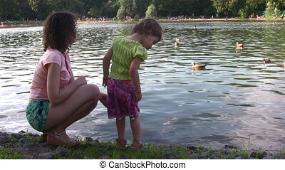 mother with girl and ducks on pond