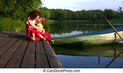 Mother with girl on pond and boat