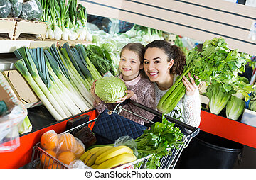 Mother with girl purchasing shallot
