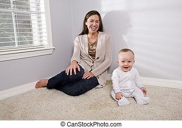 Mother with happy baby sitting on the carpet