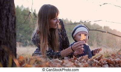 Mother with her baby boy in autumn forest falling leaves