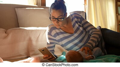 Mother with her baby boy using mobile phone 4k