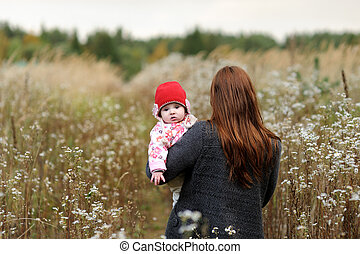 Mother with her baby girl in a meadow
