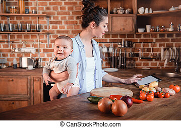 Mother with her baby son looking for recipe on digital tablet before cooking dinner in the kitchen