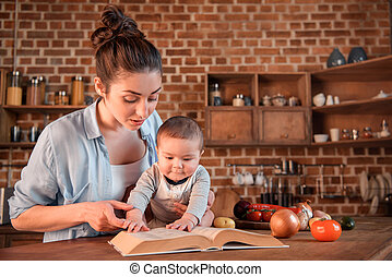 Mother with her baby son reading recipe book before preparing dinner in the kitchen