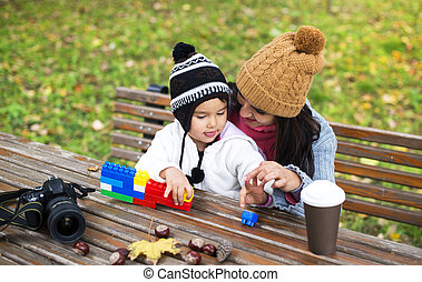 mother with her child play in park playing with blocks