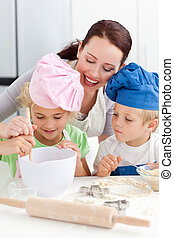 Mother with her children baking together in the kitchen