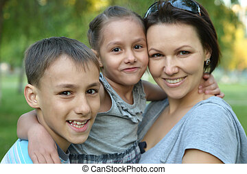 Mother with her children in summer park