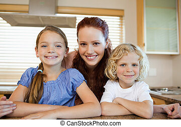 Mother with her children in the kitchen
