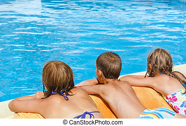 Mother with her children near swimming pool.