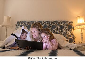Mother with her children using digital tablet under blanket...