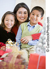 Mother With Her Daughter And Son Holding Christmas Gifts