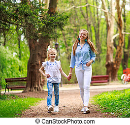 Mother with her daughter are walking in city summer park