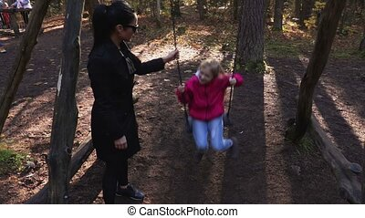 Mother with her daughter at the swing
