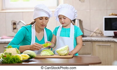 mother with her daughter cut cabbage