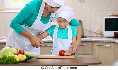 mother with her daughter cut tomato