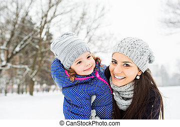 Mother with her daughter hugging outside in winter nature