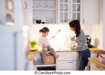 Mother with her daughter in the kitchen cooking together -...