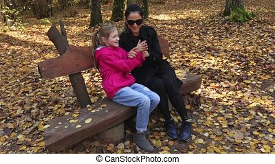 Mother with her daughter in the park on the bench