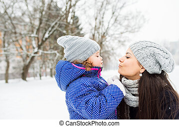Mother with her daughter kissing outside in winter nature