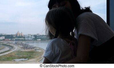 Mother with her daughter looking out of window
