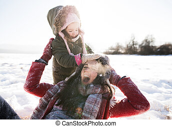 Mother with her daughter, playing in the snow.