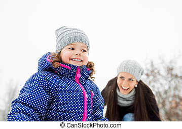 Mother with her daughter playing outside in winter nature