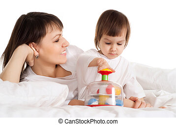 Mother with her daughter playing with a toy