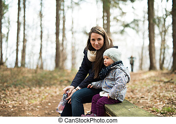 Mother with her daughter sitting on bench in forest