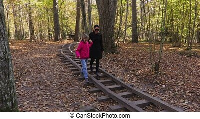 Mother with her daughter walking through the playground rails in the park