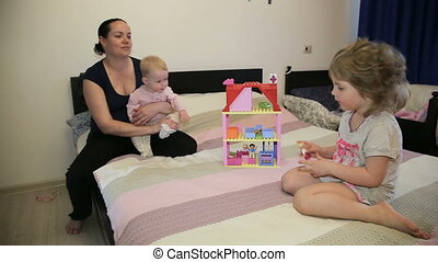Mother with her daughters in the bedroom.