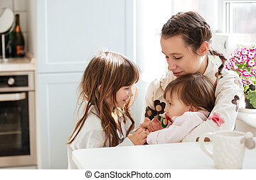 Mother with her daughters sitting in kitchen