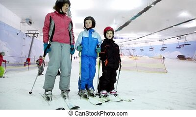 Mother with her kids stand on ski and talk