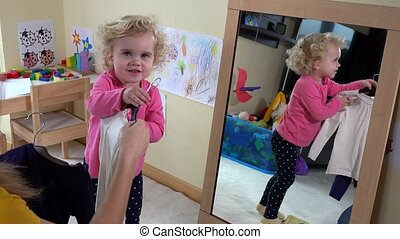 Mother with her little daughter girl measuring clothes in front of mirror
