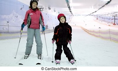Mother with her little daughter stand on ski and sway