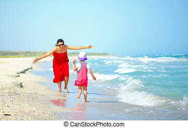 mother with her little girl playing on the seashore
